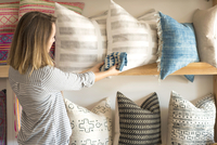 Rear view of female interior designer trying textile against cushions in retail studio