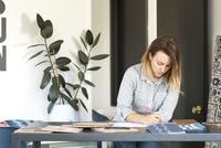 Female interior designer drawing designs at desk in retail studio 11015309761| 写真素材・ストックフォト・画像・イラスト素材|アマナイメージズ