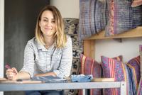 Portrait of female interior designer drawing designs at desk in retail studio 11015309762| 写真素材・ストックフォト・画像・イラスト素材|アマナイメージズ