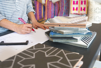 Mid section of female interior designer drawing designs at desk in retail studio 11015309765| 写真素材・ストックフォト・画像・イラスト素材|アマナイメージズ