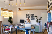 Portrait of female interior designer using laptop at desk in retail studio 11015309771| 写真素材・ストックフォト・画像・イラスト素材|アマナイメージズ