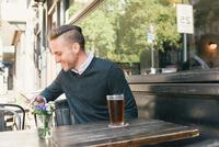 Young man sitting outside bar, using smartphone 11015309823| 写真素材・ストックフォト・画像・イラスト素材|アマナイメージズ