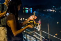 Young woman by Ping River in Chiang Mai during Loy Krathong Lantern Festival, releasing floating lantern down the Ping River, Ch 11015309856| 写真素材・ストックフォト・画像・イラスト素材|アマナイメージズ