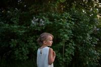 Little girl, green bushes in background 11015309890| 写真素材・ストックフォト・画像・イラスト素材|アマナイメージズ