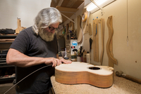 Guitar maker in workshop manufacturing guitar