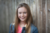 Young girl with braces smiling, wooden panelling background 11015310074| 写真素材・ストックフォト・画像・イラスト素材|アマナイメージズ