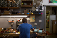 Rear view of guitar maker sitting at desk manufacturing guitar 11015310196| 写真素材・ストックフォト・画像・イラスト素材|アマナイメージズ