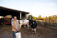 Portrait of farmer on farm, holding animal feed
