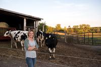Portrait of female farmer on farm, cows in background
