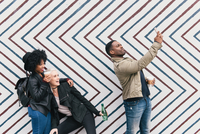 Friends taking selfie in front of zig zag pattern wall