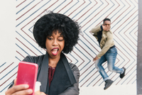 Woman taking selfie with friend in front of zig zag pattern wall