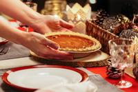 Woman placing pie on festive table 11015310400| 写真素材・ストックフォト・画像・イラスト素材|アマナイメージズ