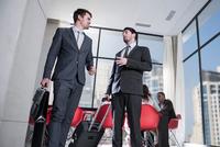 Two businessmen arriving in hotel lobby
