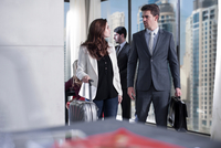 Businesswoman and man arriving in hotel lobby