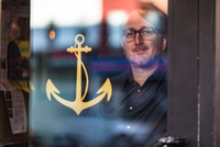 Portrait of barman looking through public house window, Brooklyn, New York, USA 11015310639  写真素材・ストックフォト・画像・イラスト素材 アマナイメージズ