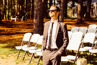 Mid adult man standing in front of rows of chairs, outdoors, in rural setting 11015310874| 写真素材・ストックフォト・画像・イラスト素材|アマナイメージズ