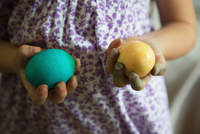 Mid section of girl holding blue and yellow dyed easter eggs