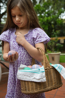Girl carrying basket of dyed easter eggs in garden
