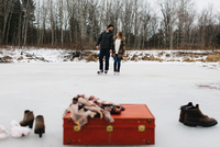 Red suitcase, boots, shawl, couple skating in background, Whitby, Ontario, Canada 11015311361| 写真素材・ストックフォト・画像・イラスト素材|アマナイメージズ