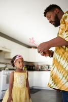 Mature man repairing fairy wand for daughter in kitchen 11015311768| 写真素材・ストックフォト・画像・イラスト素材|アマナイメージズ