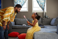 Man playing with daughter in fairy costume in living room 11015311770| 写真素材・ストックフォト・画像・イラスト素材|アマナイメージズ