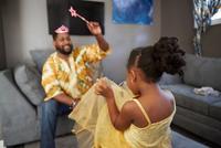 Man casting spell on daughter in fairy costume in living room 11015311772| 写真素材・ストックフォト・画像・イラスト素材|アマナイメージズ