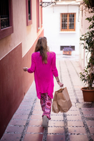 Rear view of female tourist strolling down alley with shopping bags, Marbella, Spain 11015311958| 写真素材・ストックフォト・画像・イラスト素材|アマナイメージズ