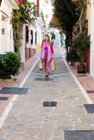 Mature female tourist strolling down alley with shopping bags, Marbella, Spain 11015311959| 写真素材・ストックフォト・画像・イラスト素材|アマナイメージズ