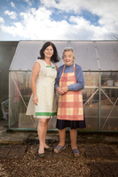 Mother and adult daughter in front of greenhouse 11015312084| 写真素材・ストックフォト・画像・イラスト素材|アマナイメージズ