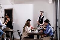 Waiter serving diners in restaurant 11015312097| 写真素材・ストックフォト・画像・イラスト素材|アマナイメージズ