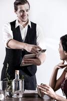 Waiter serving diner in restaurant, waiter using digital tablet 11015312099| 写真素材・ストックフォト・画像・イラスト素材|アマナイメージズ