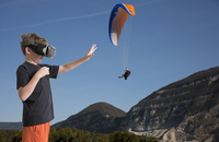 Young boy wearing virtual reality headset, reaching out to touch paraglider, digital composite