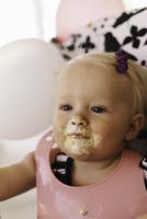 Baby girl sitting in high chair, cake around mouth 11015312243| 写真素材・ストックフォト・画像・イラスト素材|アマナイメージズ