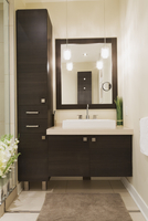Contemporary brown laminated wood vanity with mirror in bathroom of renovated ground floor apartment in old residential cottage