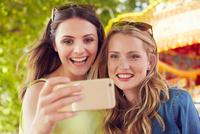 Women taking selfie, carousel in background, London, UK 11015312812| 写真素材・ストックフォト・画像・イラスト素材|アマナイメージズ