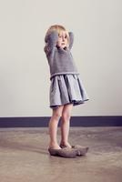 Girl standing in vintage wooden clogs with hands behind head 11015312865| 写真素材・ストックフォト・画像・イラスト素材|アマナイメージズ