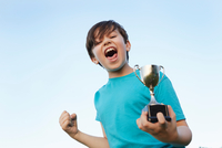 Boy making fist and holding sport trophy against blue sky 11015312916| 写真素材・ストックフォト・画像・イラスト素材|アマナイメージズ