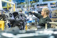 Female apprentice engineer on production line in car factory 11015313102| 写真素材・ストックフォト・画像・イラスト素材|アマナイメージズ