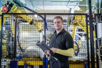 Portrait of apprentice engineer operating robots on production line in car factory 11015313112| 写真素材・ストックフォト・画像・イラスト素材|アマナイメージズ