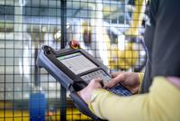 Apprentice engineer operating robots on production line in car factory, close up 11015313113| 写真素材・ストックフォト・画像・イラスト素材|アマナイメージズ