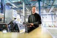 Portrait of apprentice engineer on production line in car factory 11015313118| 写真素材・ストックフォト・画像・イラスト素材|アマナイメージズ