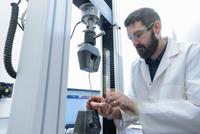 Scientist testing tensile strength of cable in laboratory 11015313207| 写真素材・ストックフォト・画像・イラスト素材|アマナイメージズ