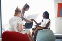Woman handing takeaway coffee to businesswomen sitting on beanbags 11015313549| 写真素材・ストックフォト・画像・イラスト素材|アマナイメージズ
