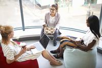 Three businesswomen with takeaway coffee sitting on beanbags chatting 11015313551| 写真素材・ストックフォト・画像・イラスト素材|アマナイメージズ