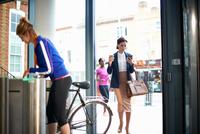 Women arriving at entrance to work 11015313572| 写真素材・ストックフォト・画像・イラスト素材|アマナイメージズ