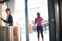 Women arriving at entrance to work 11015313573| 写真素材・ストックフォト・画像・イラスト素材|アマナイメージズ