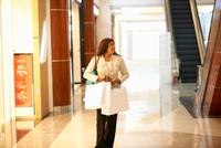 Mature woman carrying shopping bags in shopping mall, Dubai, United Arab Emirates 11015313614| 写真素材・ストックフォト・画像・イラスト素材|アマナイメージズ