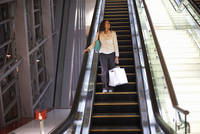 Mature woman with shopping bags moving down escalator in shopping mall, Dubai, United Arab Emirates 11015313618| 写真素材・ストックフォト・画像・イラスト素材|アマナイメージズ