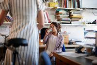 Woman in office drinking coffee chatting to colleague 11015313635| 写真素材・ストックフォト・画像・イラスト素材|アマナイメージズ