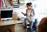 Woman sitting on desk looking at notepad 11015313637| 写真素材・ストックフォト・画像・イラスト素材|アマナイメージズ